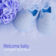 Knitted baby shoes for boy on a blue background. Greeting card.  — Stock Photo