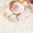 Female hands in mittens Christmas tree ball, on snow background. — Stock Photo