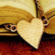 Stock Photo: Small golden heart on a book.