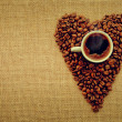 Heart shape made from coffee beans with cup of coffee on linen fabric. — Stock Photo #35547103