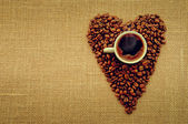 Heart shape made from coffee beans with a cup of coffee on linen fabric. — Stock Photo