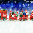 Santa Claus in a toy train with gifts, snowman and christmas tree.  — Stock Photo