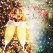 Champagne glasses against christmas tree bokeh lights — Stockfoto