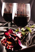 Wine and rose on the black satin. — Stock Photo