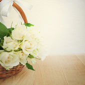 Wicker basket of white roses on wooden table. — Stock Photo