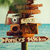 Travel and vacation concept. Direction to different places of the world indicated on the sign with old camera. — Stock Photo