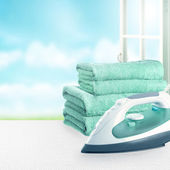Pile of towels and smoothing-iron on the table. — Stock Photo