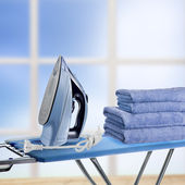 Pile of towels and smoothing-iron on the ironing board — Stock Photo