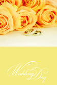 Wedding rings and roses bouquet — Stock Photo