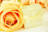 Bouquet of roses and gift box on white background — Stock Photo