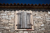 Old window with closed shutters — Stock Photo