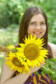 Pretty green eyes woman with sunflowers — Stock Photo