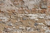 Ancient red brick wall with remaining plaster spots — Stock Photo
