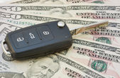 Car keys over dollar banknotes — Stock Photo