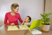 Happy woman helping small kid write — Stock Photo