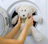 Woman loading fluffy toy in the washing machine — Stock Photo