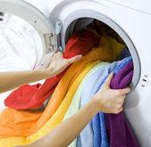 Vrouw die kleur kleding van wasmachine — Stockfoto