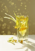 Glass of lime tea and linden flowers — Stock Photo