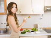 Girl eating a greek salad in the kitchen — Stok fotoğraf