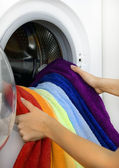 Woman taking color laundry from washing machine — Stock Photo
