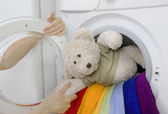 Woman taking fluffy toy from washing machine — Stock Photo