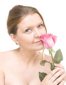 Attractive mid adult woman with a pink rose, female face of beau — Stock Photo