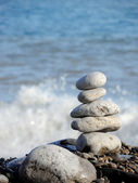 Close-up of white pebbles stack over blue sea. — Stock Photo