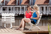 Deux belles amies au repos sur le banc et parler — Photo