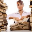 Beautiful young woman with stack of books - Stockfoto