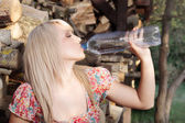 Beautiful country girl drinking — Stock Photo