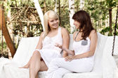 Two beautiful female friends resting on swing and talking — Stock Photo