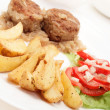 Meatballs with stewed onion and fried potato wedges - Stock Photo