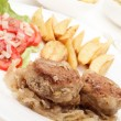 Meatballs with stewed onion and fried potato wedges - Stockfoto
