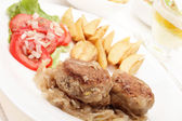 Meatballs with stewed onion and fried potato wedges — Stock Photo