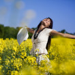 Woman in the yellow rape field — Stock Photo