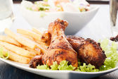 Chicken drumsticks with prepared potatoes — Stock Photo