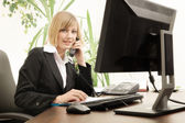 Female executive talking on phone in office — Stock Photo