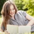 Beautiful girl reading a book and relax in the park — Stock Photo
