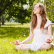 Young woman doing yoga exercises in the park — Stock Photo #26209357