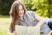 Piękna dziewczyna czytając książkę i relaksować się w parku — Zdjęcie stockowe