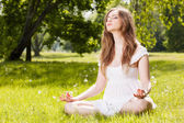 Young woman doing yoga exercises in the park — Stock Photo