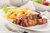 Grilled shashlik with french fries — Stock Photo