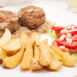 Meatballs with stewed onion and fried potato wedges — Stock Photo #29787099