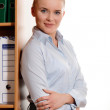 Businesswoman leaning against bookshelf — Stock Photo