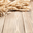 Wooden background and ears of wheat — Stock Photo