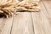 Houten achtergrond en oren van tarwe — Stockfoto