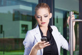 Young businesswoman at phone — Stock Photo