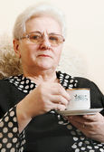 A woman with a pleasant smile enjoying a cup of tea. — Stock Photo