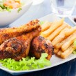 Chicken drumsticks with french fries — Stock Photo