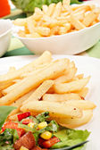 French fries and salad — Stock Photo
